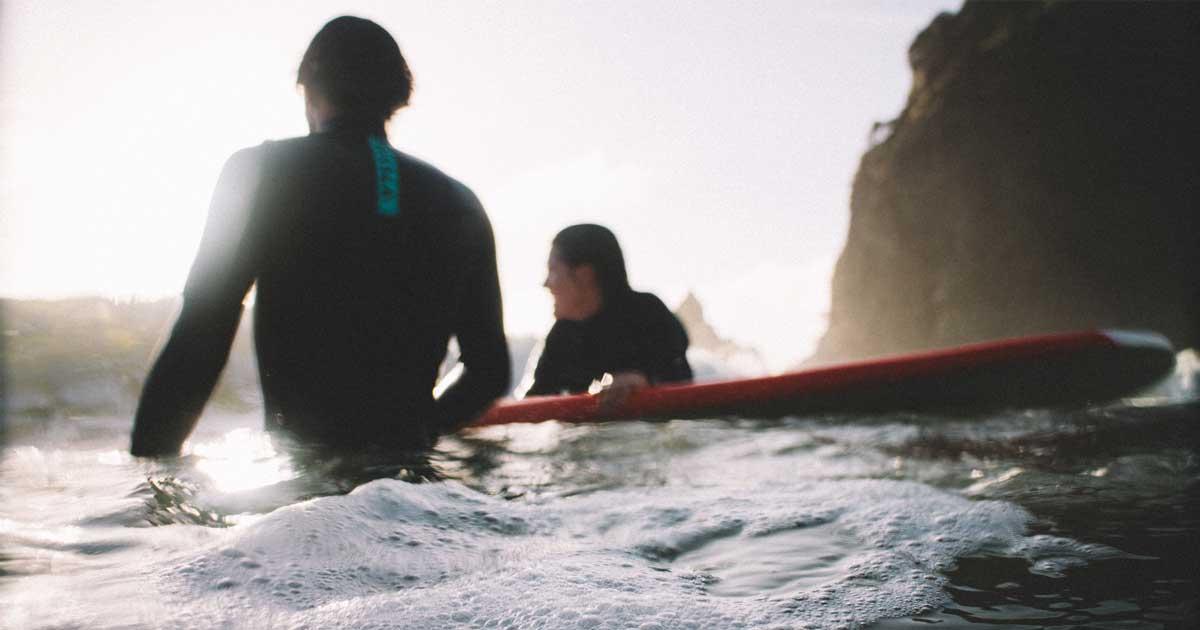 Mies ja nainen fiilistelee vedessä SUP-kurssia